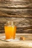 El cuenco con la miel en la tabla de madera El banco de la estancia de la miel cerca de la cuchara de madera Fotos de archivo libres de regalías