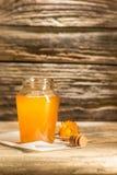 El cuenco con la miel en la tabla de madera El banco de la estancia de la miel cerca de la cuchara de madera Imagen de archivo