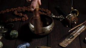 El cuenco de cobre del canto y la mano de un hombre lleva un palillo de madera sobre él almacen de video