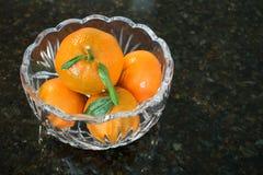 El cuenco de cristal tallado bonito llenó de las mandarinas brillantes Imagen de archivo