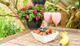 El cuenco de fresas y las bayas con un plátano y una sacudida beben Imagen de archivo libre de regalías