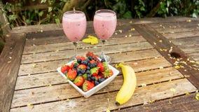 El cuenco de fresas y las bayas con un plátano y una sacudida beben Foto de archivo libre de regalías