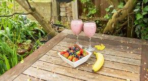 El cuenco de fresas y las bayas con un plátano y una sacudida beben Fotos de archivo libres de regalías