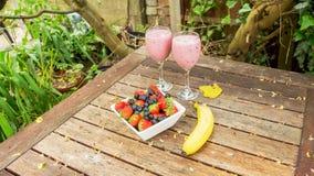 El cuenco de fresas y las bayas con un plátano y una sacudida beben Imágenes de archivo libres de regalías