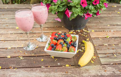 El cuenco de fresas y las bayas con un plátano y una sacudida beben Fotografía de archivo libre de regalías