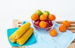 El cuenco de fruta con la manzana roja, la manzana verde y la naranja puso al lado de plato del maíz amarillo, tres naranjas pues fotos de archivo libres de regalías