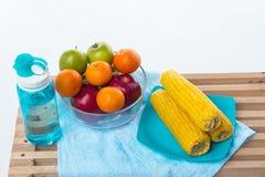 El cuenco de fruta con la manzana roja, la manzana verde y la naranja puso al lado de plato del maíz y de la botella amarillos de fotos de archivo