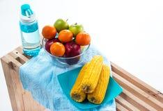 El cuenco de fruta con la manzana roja, la manzana verde y la naranja puso en el centro del plato amarillo del maíz y la botella  foto de archivo