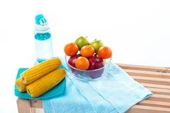 El cuenco de fruta con la manzana roja, la manzana verde y la naranja puso en el lado derecho del plato amarillo del maíz, al lad fotografía de archivo