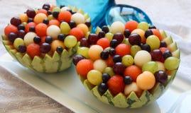 El cuenco de la sandía llenó de la sandía, las bolas de melón, las uvas verdes y púrpuras y las bayas fotografía de archivo libre de regalías