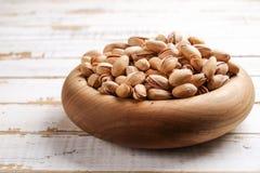 El cuenco de madera de Brown llenó de las nueces de pistacho verdes crudas en cáscara agrietada foto de archivo