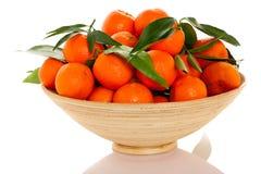 El cuenco de madera llenó de los agrios anaranjados frescos del mandarín con Imágenes de archivo libres de regalías