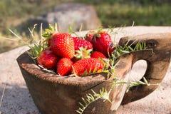 El cuenco de madera viejo llenó las fresas rojas maduras frescas jugosas en una piedra vieja vieja Imagenes de archivo