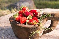 El cuenco de madera viejo llenó las fresas rojas maduras frescas jugosas en una piedra vieja vieja Foto de archivo