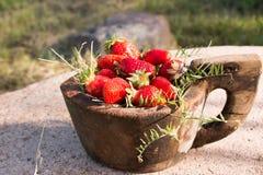 El cuenco de madera viejo llenó las fresas rojas maduras frescas jugosas en una piedra vieja vieja Imagen de archivo