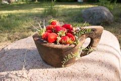 El cuenco de madera viejo llenó las fresas rojas maduras frescas jugosas en una piedra vieja vieja Fotografía de archivo libre de regalías