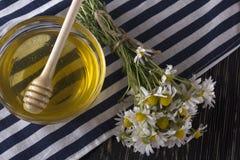 El cuenco de miel, de vidrio con leche y de manzanilla florece Imagen de archivo