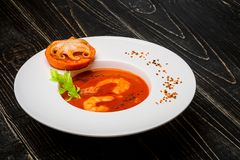 El cuenco de sopa del tomate con los camarones con un pequeño pulpo coció en una rebanada anaranjada en un fondo de madera negro, Foto de archivo