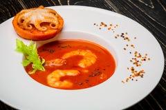 El cuenco de sopa del tomate con los camarones con un pequeño pulpo coció en una rebanada anaranjada en un fondo de madera negro, Imagenes de archivo