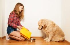 El cuenco del animal doméstico de relleno de la muchacha cuidadosa con forraje seco Fotografía de archivo