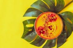 El cuenco del Smoothie con el pensamiento comestible florece, las semillas del chia, berrie del goji fotos de archivo libres de regalías