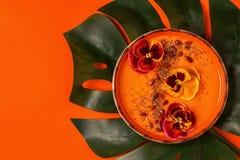 El cuenco del Smoothie con el pensamiento comestible florece, las semillas del chia, berrie del goji imagen de archivo