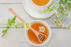 El cuenco llenó de la miel y de la cuchara de la flor con una taza de té Fotografía de archivo