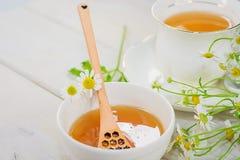 El cuenco llenó de la miel y de la cuchara de la flor con una taza de té Fotos de archivo libres de regalías