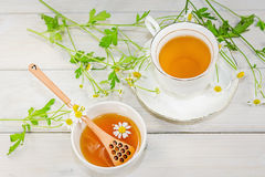El cuenco llenó de la miel y de la cuchara de la flor con una taza de té Foto de archivo libre de regalías