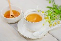 El cuenco llenó de la miel y de la cuchara de la flor con una taza de té Fotografía de archivo libre de regalías