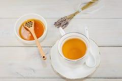 El cuenco llenó de la miel y de la cuchara de la flor con una taza de té Imagen de archivo libre de regalías