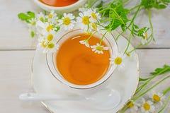 El cuenco llenó de la miel y de la cuchara de la flor con una taza de té Fotos de archivo