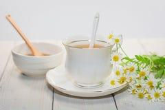 El cuenco llenó de la miel y de la cuchara de la flor con una taza de té Imagenes de archivo