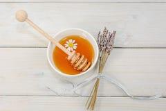 El cuenco llenó de la miel y de la cuchara de la flor con una taza de té con c Imagen de archivo