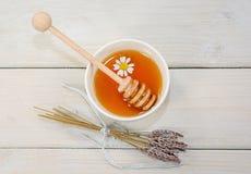 El cuenco llenó de la miel y de la cuchara de la flor con una taza de té con c Fotos de archivo