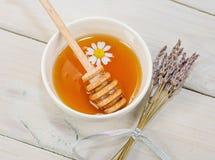 El cuenco llenó de la miel y de la cuchara de la flor con una taza de té con c Imagen de archivo libre de regalías