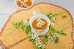 El cuenco llenó de la miel y de la cuchara de la flor con una taza de té en una d Imagenes de archivo