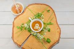 El cuenco llenó de la miel y de la cuchara de la flor con una taza de té en una d Foto de archivo