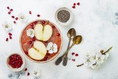El cuenco rosado con las semillas del chia, granada del smoothie de los superfoods, cortó manzanas y la miel Visión de arriba, su Foto de archivo libre de regalías