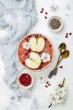 El cuenco rosado con las semillas del chia, granada del smoothie de los superfoods, cortó manzanas y la miel Visión de arriba, su Imágenes de archivo libres de regalías