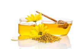 El cuenco y el tarro de miel cerca de una pila de polen y de flor Foto de archivo libre de regalías