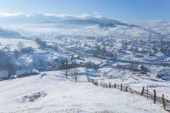 El cuento de hadas del invierno, nevadas cubrió los árboles y las casas en el pueblo de montaña Fotografía de archivo libre de regalías