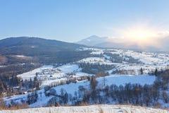 El cuento de hadas del invierno, nevadas cubrió los árboles y las casas en el pueblo de montaña Fotos de archivo libres de regalías