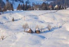 El cuento de hadas del invierno, nevadas cubrió los árboles y las casas en el pueblo de montaña Imagen de archivo