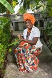 El cuerpo completo vertical de una mujer afroamericana alegre que lleva un vestido nacional colorido brillante se sienta en el ja imagen de archivo