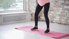 El cuerpo de la mujer delgada joven, haciendo se pone en cuclillas en un pasillo del club de fitness metrajes