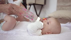 El cuidado de la madre, bebé recién nacido está mintiendo en cama y el agua potable de una botella que los controles de la mamá e metrajes