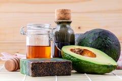 El cuidado de piel alternativo y friega el aguacate fresco, aceites, miel Imagen de archivo libre de regalías