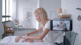El cuidado maternal, vlogger de la mamá enseña a cómo cambiar al niño recién nacido de la ropa mientras que registra el vídeo de  metrajes