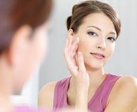El cuidar de la mujer de su piel hermosa en la cara Imagen de archivo libre de regalías